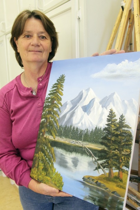 Artists' Co-op member Donna Goldthorpe with one of her landscape paintings, one of many works on display at the group's new location in the 3955 Hart Highway building. Teresa MALLAM/Free Press