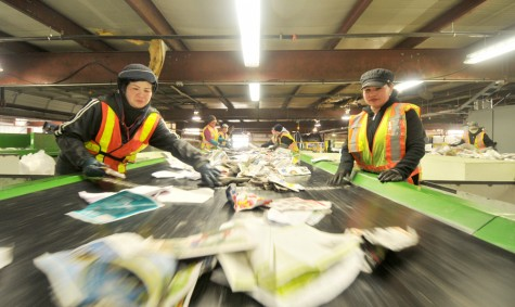 Workers sort out contaminants at Emterra Environmental's material recovery facility in Surrey. The plant is one of three that will process recyclables collected for Multi-Material BC.