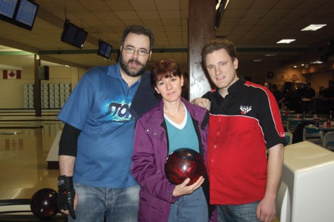 Susan Burkitt, Duffy Lougheed's niece, holds Duffy's bowling ball, accompanied by Ryan Paziuk, left, and Leif Skggedal, two of the bowlers who gathered at the Str1ke Zone recently to raise funds in memory of Lougheed. Allan WISHART/Free Press