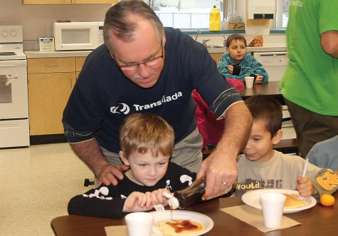 Scott Bone of TransCanada pours syrup on a pancake for some of the Ron Brent Elementary students taking part in the breakfast program at the school on Monday. TransCanada has partnered with Breakfast Club of Canada to fund the program. Allan WISHART/Free Press