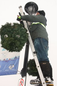 A volunteer from the Activator Society installs a hanging basket along George Street on Sunday. A pilot project of the Downtown Prince George Business Improvement Association, the 50 decorative baskets contain re-purposed artificial Christmas trees donated by the public. Teresa MALLAM/Free Press