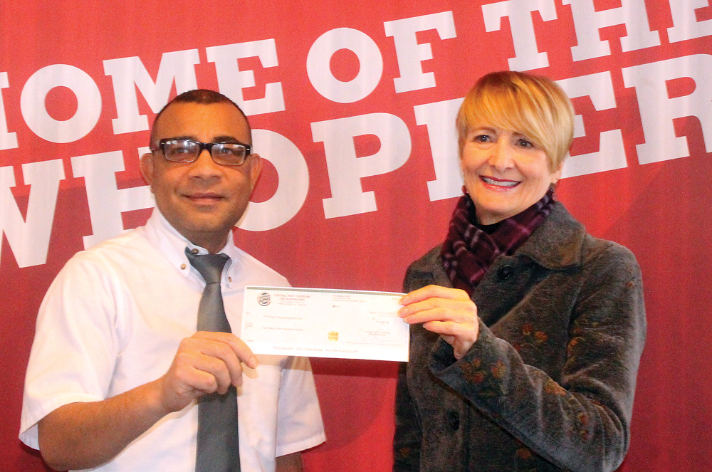 Burger King general manager Deepark Chaudhury presents a cheque for $1,000 to Community Policing co-ordinatior Linda Parker. The money was raised during a fundraiser at the end of November. Parker said it will bot to the group's Youth at Risk team. Allan WISHART/Free Press