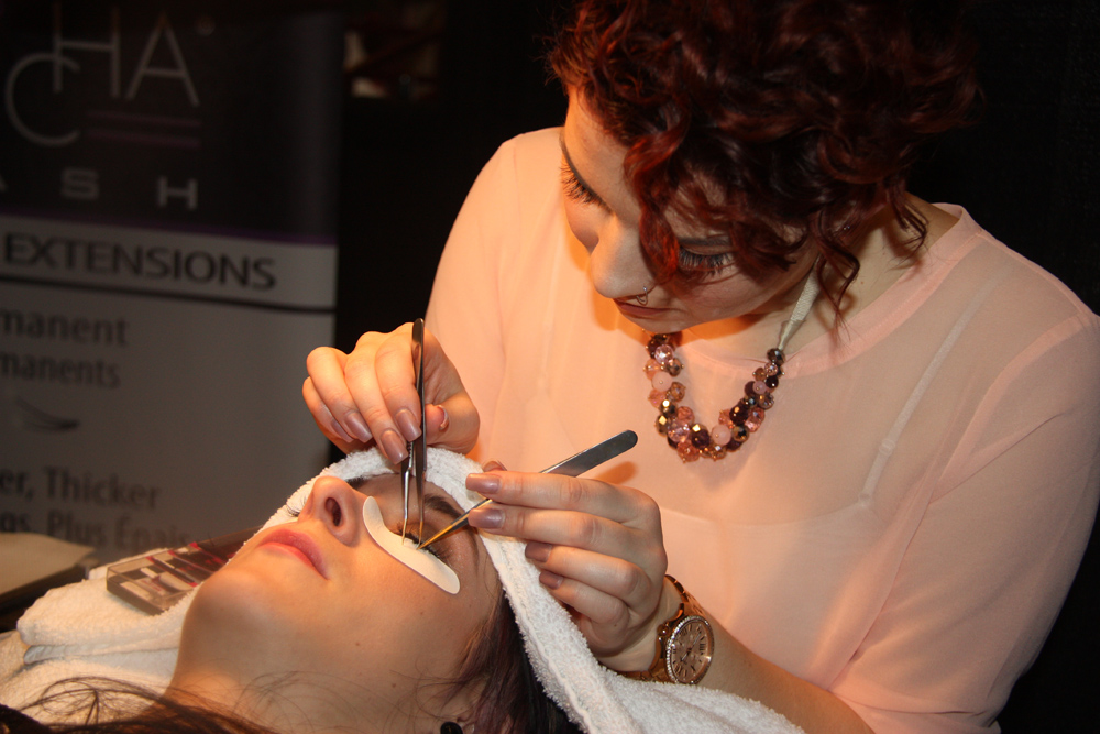 Quinn Abrahamse, salon coordinator with Shine Hair Salon, gives eyelash extensions to a bride-to-be at the Storybook Wedding Bridal Expo Sunday at the Prince George Civic Centre. Teresa MALLAM/Free Press