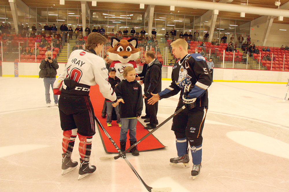 Cariboo Cougars captain Auston Gray, left, and Kootenay Ice captain Kyle Chermenkoff shake hands with Jameson Jones after the ceremonial faceoff before their B.C. Major Midget League game Saturday at Kin 1. The night was a fundraiser for BC Children's Hosptal, where Jameson, a cancer survivor, spent a lot of time while undergoing treatment.