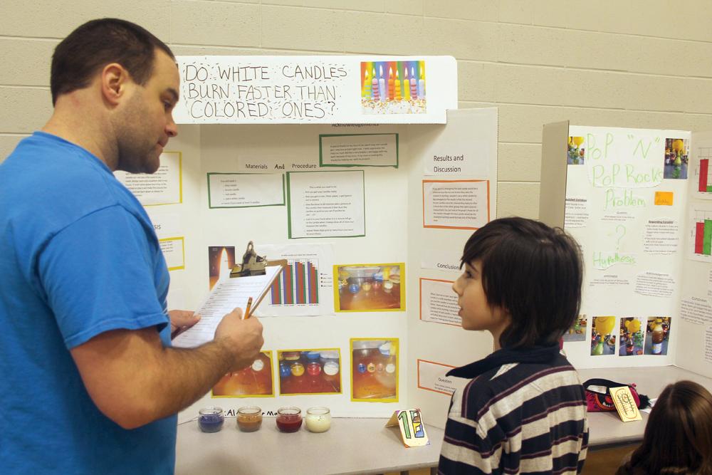 Foothills Elementary student Alexander Martinez describes his science fair project to judge Laird Schade. Allan WISHART/Free Press