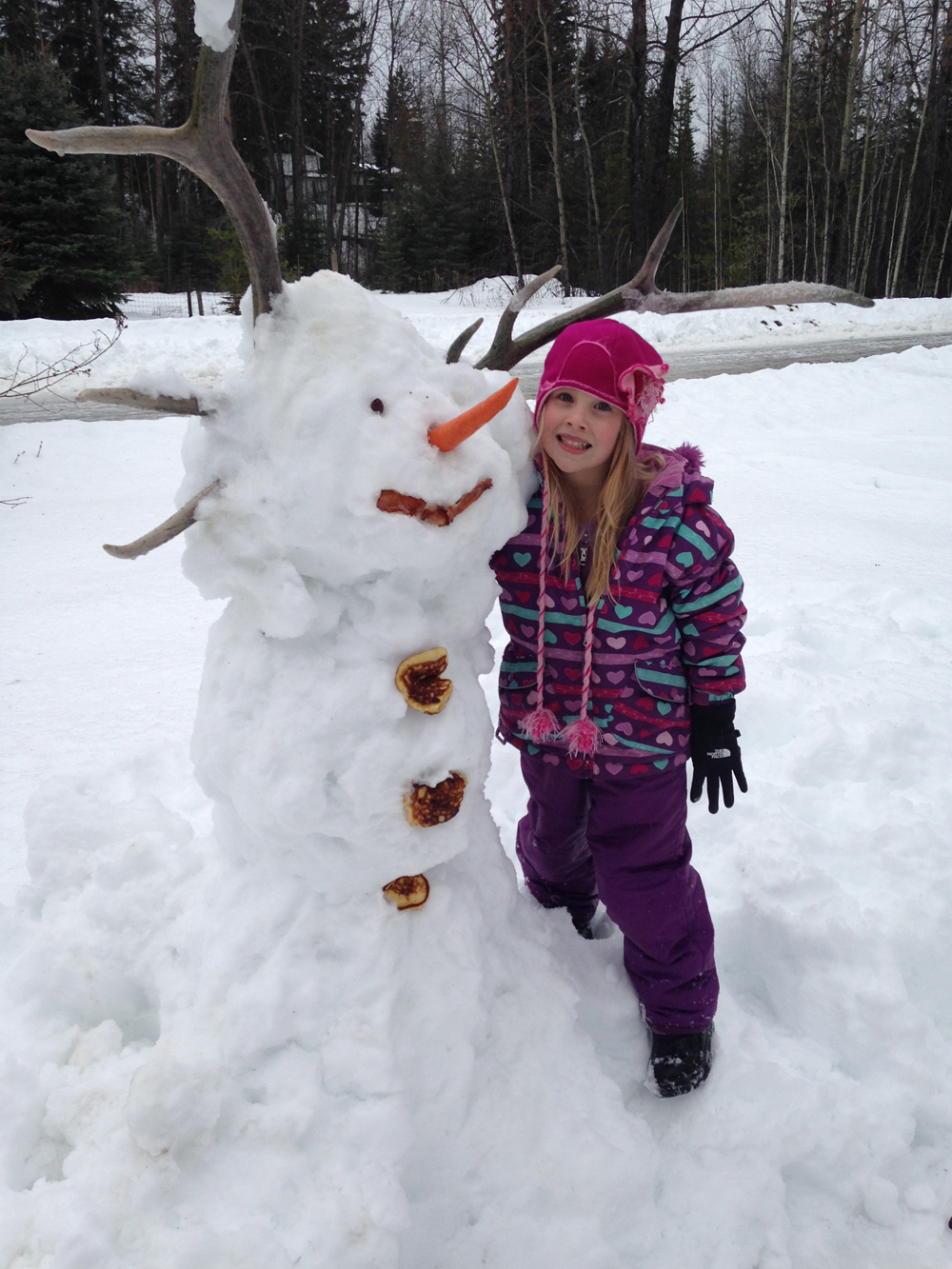 Marijke Suter with the snowman she made visiting her Auntie  Patsy in Hixon. Marijke is five years old and worked very hard to build this unique snowman.  He has beautiful horns and leftover breakfast for his mouth and buttons, and a carrot nose. Auntie Patsy and Uncle Larry are very proud to show off this snowman in their yard. It is her entry in the Snow Daze Snowman Building contest, which is part of Mardi Gras.