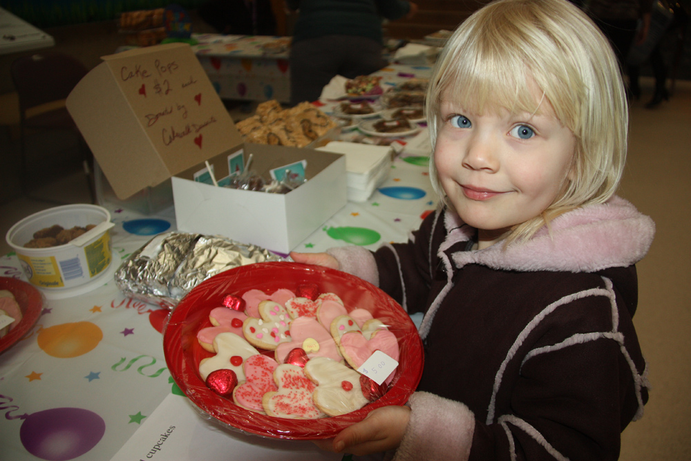 Happy Valentine's Day... Adelynne Cote who turned five years old Thursday, finds a plate of Valentine's Day cookies and chocolates at a UHNBC fundraiser bake sale put on by staff. Teresa MALLAM/Free Press