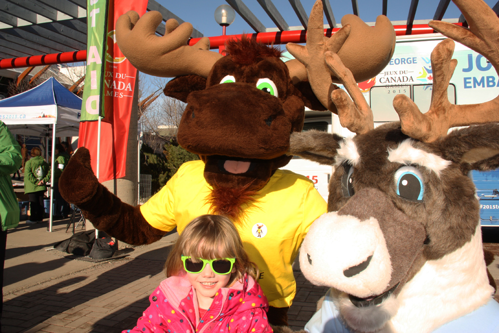 Ruby Osberg, 3, enjoys the sunshine at Canada Winter Games village  Friday with her pals Tourism B.C.'s Fraser the Moose, left, Northern Health's Spirit the Cariboo. Teresa MALLAM/Free Press