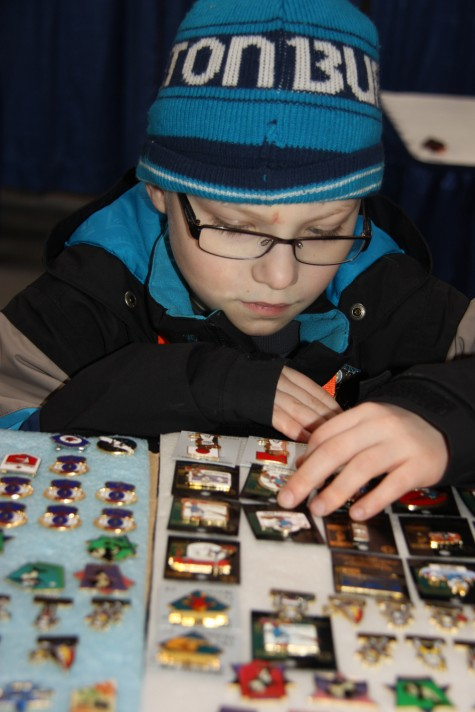 Young collector Cole Dawe admires a selection of Games pins at a trading booth Sunday at the Commonwealth building. Teresa MALLAM/Free Press