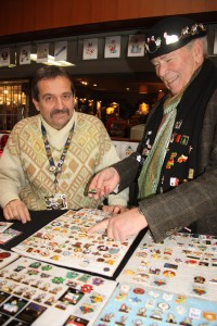 Pin collector Gary Clarke checks out Games pins at Krassi's (the trader prefers to use his first name only) table on Sunday at the Commonwealth Building. Teresa MALLAM/Free Press