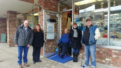 Ralph Allan (PG Accessibility Committee), left, Sharon Doerksen, LSD owner, Lorraine Young (Handy Circle,) Ross Pullan (CNC Carpentry,) Ken Biron (Accessiblity Committee) and Jean Allan (Ralph's wife celebrate a milestone as a portable ramp to assist people with mobility issues is set outside a downtown business on Tuesday.