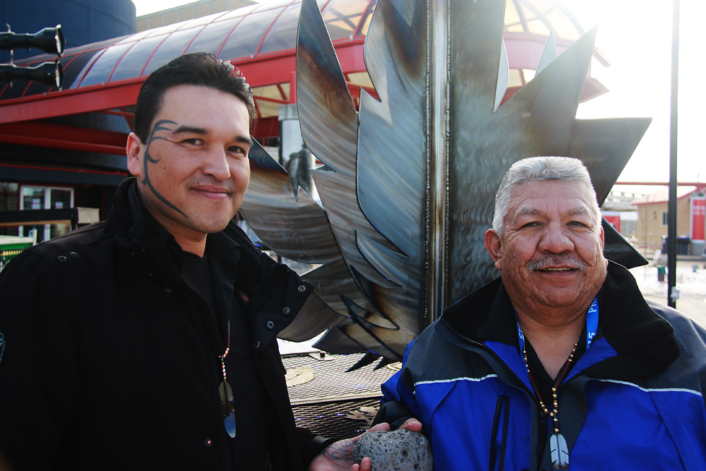Artist Clint George, left, and Chief Dominic Frederick with Gathering of the Rocks Sculpture on Wednesday at the Canada Games Plaza. The sculpture  will become one of the legacies of the 2015 Canada Winter Games and close to 1,500 rocks, of all sizes, from all over the country will eventually find a home inside the metal sculpture. The new artwork which has the maple leaf sitting on a First Nations drum, was unveiled in a special outdoor ceremony attended by Mayor Lyn Hall and several council members, Studio 2880 artist and executive director Wendy Young, Mike Davis, Games executive and several other dignitaries. Teresa MALLAM/Free Press