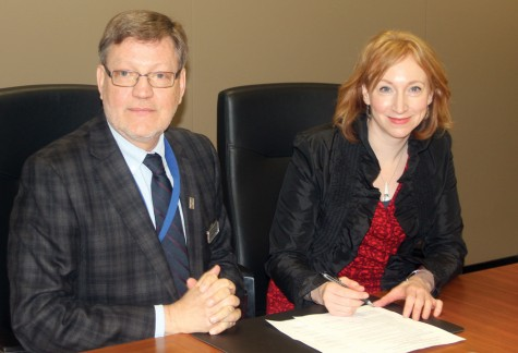 CNC President Henry Reiser, left, and Catherine Pennington of Norther Gateway sign an agreement Monday which will see Northern Gateway donate $250,000 to the new Digital Delivery Initiative at CNC.