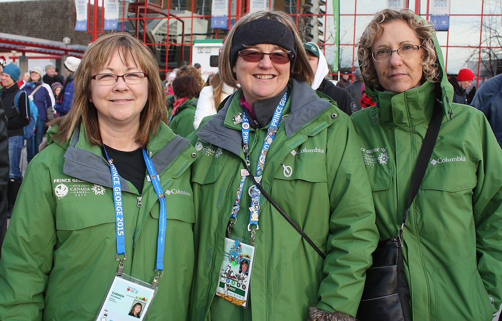 The 2015 Canada Winter Games relied heavily on volunteers, readily identifiable by their green jackets. Three of the 4,500 volunteers Carmen Wildeman, left, who volunteered in planning, Tammy LeDuke, security, and Faye Jarabek, finance and administration, take in the closing ceremonies at Canada Games Plaza. Bill PHILLIPS/Free Press