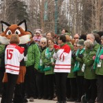 """Some of the thousands of """"green jacket"""" volunteers – 4,500 in total – who worked tirelessly for two weeks get some photos in and a visit with 2015 Canada Winter Games Mascot Naguz just before official Closing Ceremonies commence at the Agora at UNBC. Teresa MALLAM/Free Press"""
