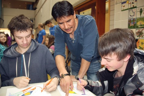 First Nations artist and carver Michael Antoine checks in with Reed Scales (left) and Scott Monroe, both of McBride, on Wednesday as they work on colouring in traditional motifs during Aboriginal Days held at CNC's Gathering Place. Teresa MALLAM/Free Press