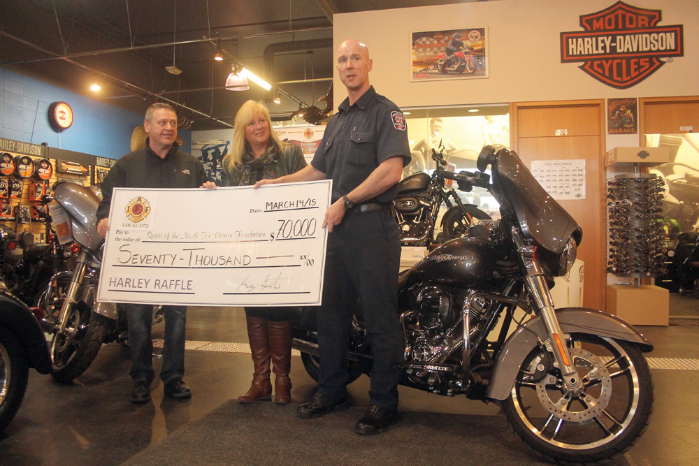 Spirit of the North Healthcare Foundation Board director Darcy Bryant, left, and CEO Judy Neiser accept a cheque for $70,000 from Greg Houston of the Prince George Fire Fighters. The money is the proceeds from the annual Harley-Davidson Raffle the firefighters hold, and this year will be used to help purchase a Giraffe Omni Bed for the care of newborns. Allan WISHART/Free Press