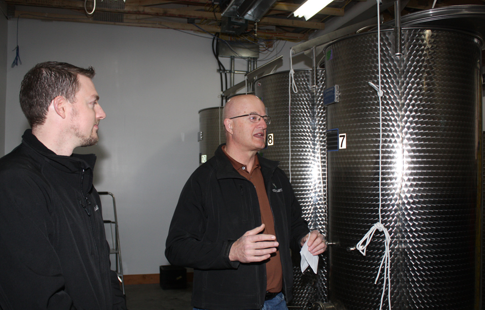 Doug Bell and Pat Bell of Northern Lights Estate Winery talk to guests during the 'tossing of the yeast' ceremony Friday. The tossing of the yeast gets the process of actually making wine underway at the winery. Bill PHILLIPS/Free Press