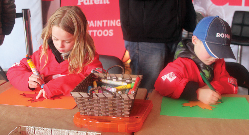 Ella, left, and Austin Stevenson draw outlines of a maple leaf as they create their own signs at Hometown Hockey on Sunday at the Exhibition Grounds. Allan WISHART/Free Press