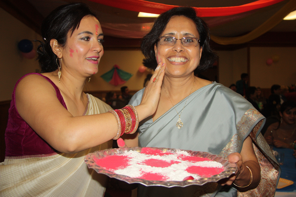 Mina Bhandari (left) and Madhu Singh carry a tray with hot pink coloured powders to put on the faces of participating guests at Holi (Festival of Colours) celebrations on Saturday at Day's Inn. When the colours go on, tradition has it that gripes and grievances go away, replaced by love and forgiveness of others.  Teresa MALLAM/Free Press