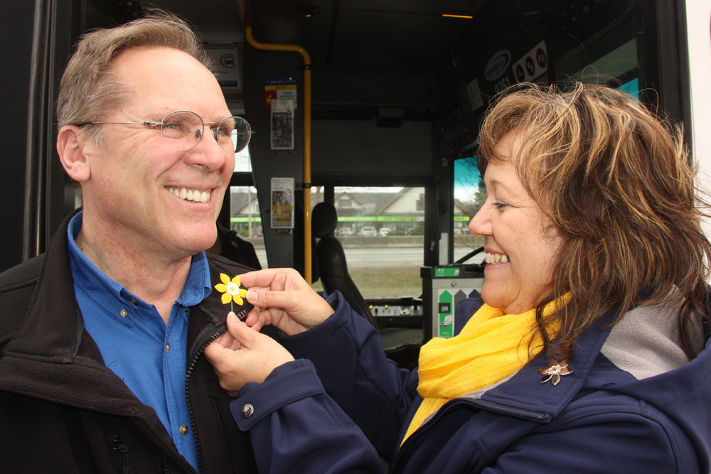 "Prince George transit bus drivers will be greeting passengers with a little more colour in the coming weeks. On Tuesday, Marjo van Helvoirt Koop, a coordinator with the Canadian Cancer Society (and Dave Bradshaw, City of Prince George manager Parks, Transit and Public Waste) was giving out pins bearing the yellow daffodil motif to local bus drivers. Shown here, transit driver Jeff Waters gets ""pinned"" before continuing along his bus route from Spruceland mall. Teresa MALLAM/Free Press"