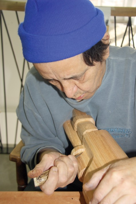Lenard Paquette Jackson, aboriginal artist in residence at Two Rivers Gallery, whittles and works away at a new carving project, Inside House Post, which will feature the Three Watchmen who in First Nations culture are protectors of the people and warn of danger coming. The artist is happy to talk about his work with visitors who stop by the gallery. Teresa MALLAM/Free Press