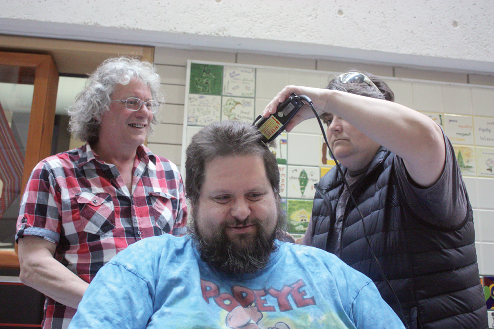 CNC business instructor Bruce Bennett watches as student Kim Hurtubise takes the first few swaths of Mark Wendling's hair. The two instructors got their heads shaved Wednesay morning to raise funds for the Canadian Cancer Society. Allan WISHART/Free Press