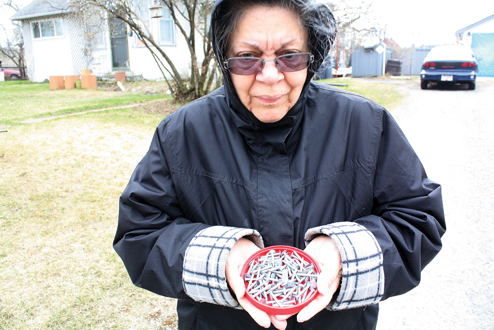 Cheryll Hallam, who lives on 11th Avenue, shows off a bunch of roofing nails she collected off the street in front of her house. Over the past six months the Prince George RCMP have received three reports of nails being distributed along streets in an area near the University Hospital of Northern BC. Bill PHILLIPS/Free Press