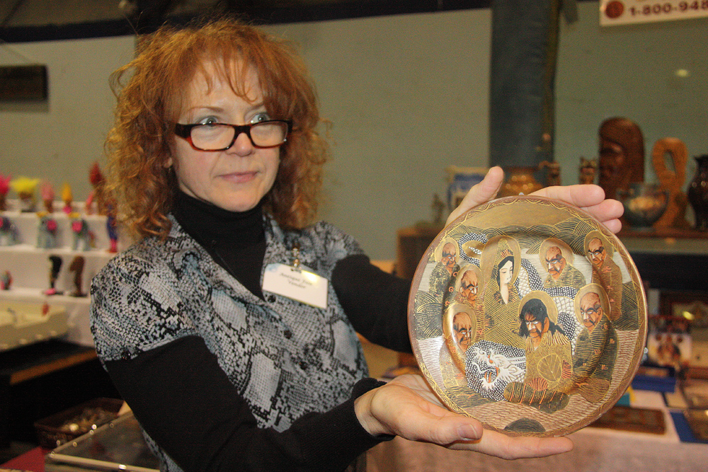 Christine Gravel from Keremeos holds up an antique Satsuma Japanese hand-painted plate circa 1900 to 1910 for a customer at the Hospice Antiques and Collectibles Fair on Sunday. Proceeds from entry fees go towards Hospice Rotary House which provides end of life care. Teresa MALLAM/Free Press