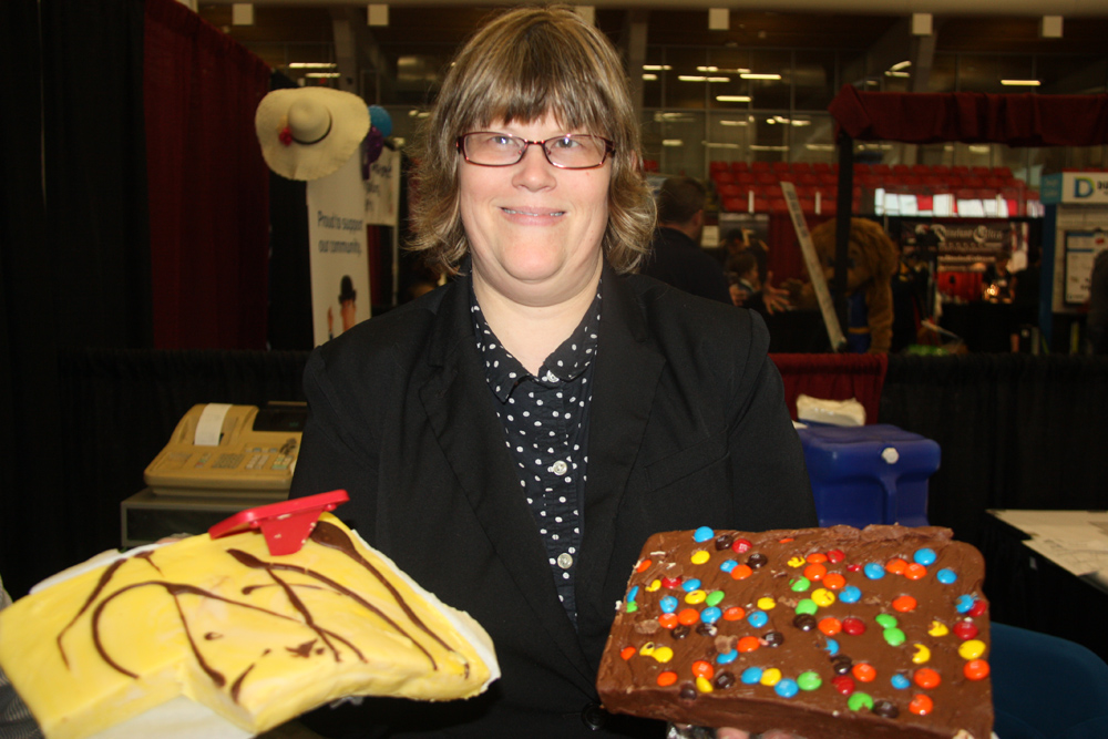 Bev Alder of Fudge and More shows off two of over 30 vararities of tasty fudge at her booth on Sunday at the Northern B.C. Home and Garden Show at the Kin Centres. Teresa MALLAM/Free Press