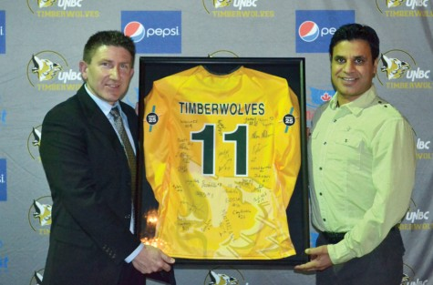 UNBC men's soccer coach Alan Alderson, left, presents Sonny Pawar with a jersey signed by current members of the team and alumni. Pawar was head coach of the Timberwolves for six years before becoming an assistant coach when the team joined the Canada West conference. Photo Courtesy UNBC Athletics